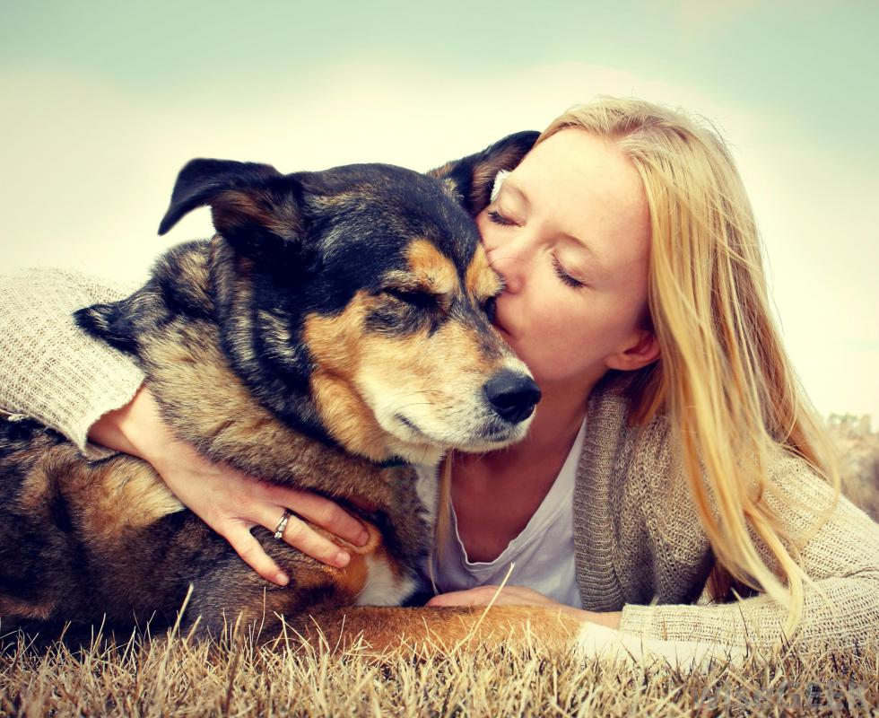 girl-kissing-old-dog-on-ground